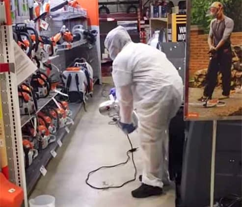 a male disinfecting a shop