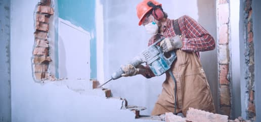 worker with personal protection equipment and demolition hammer at service for interior brick wall construction breaking