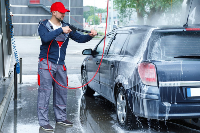 car wash worker is washing client's car